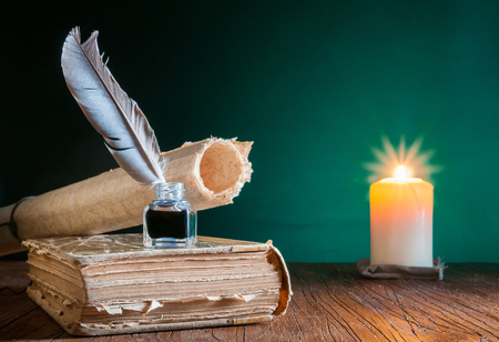 Quill pen, inkwell and a rolled papyrus sheet on an old book by candle light Фото со стока