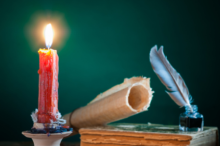 Closeup view of a candle with a quill pen and an old book in the background Stock Photo