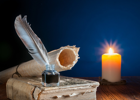 Quill pen, inkwell and a rolled papyrus sheet on an old book by candle light 스톡 콘텐츠