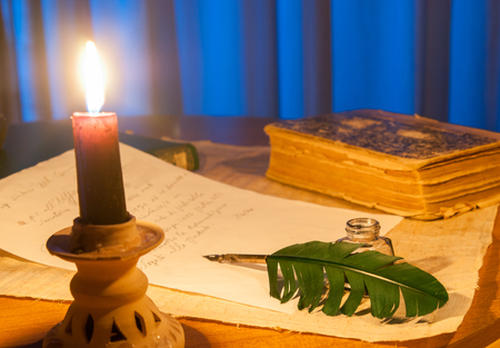 Closeup view of a candle with a quill and a letter in the background