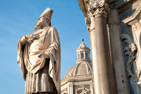One of statue outside Saint Agatha Church in Catania, Sicily, and the abbey in the background Stock Photo