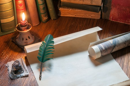 Quill pen, old papers and books by candle light