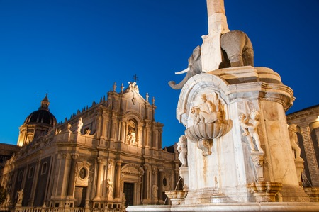 The famous lava stone elephant in the main square of Catania, Sicily, with a view of St. Agatha church