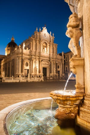 Night view of the fountain at the base of the famous lava stone elephant in the main square of Catania, Sicily, with a view of St. Agatha church