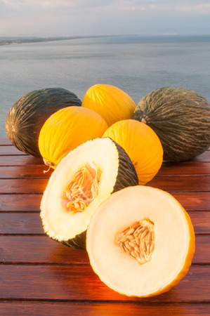 Open yellow and green melons of West Siciiy on a wooden table with blue sea and Mount Etna in the background
