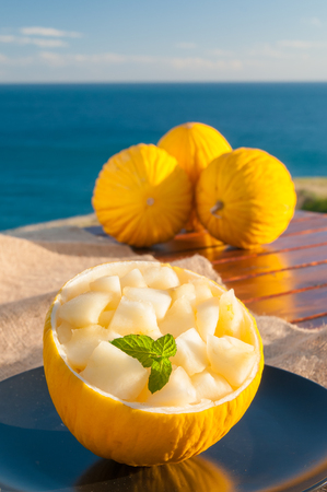 Yellow melons of West Sicily cut in cubes with blue sea in the background