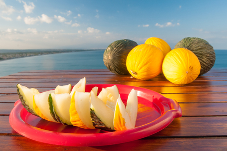 Wedges of yellow and green melons of West Siciiy on a wooden table with blue sea in the background