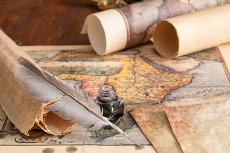 Quill pen on an old map With rolled papers Stok Fotoğraf