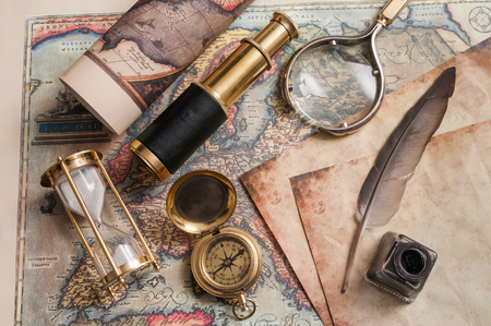 Quill pen on an old map and vintage items
