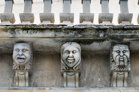 Closeup view of mascarons with  funny faces under the balcony of a baroque palace in the province of Syracuse, Sicily Editorial