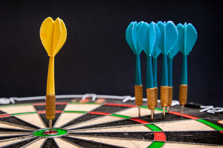 Close-up view of a yellow dart on the bullseye