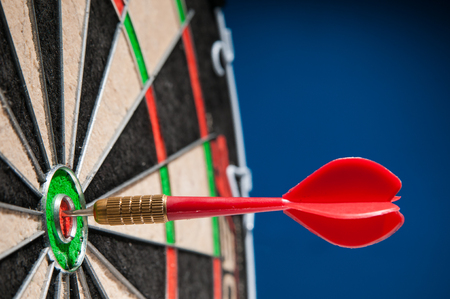Close-up view of a red dart on the bullseye of a dartboard Stock Photo