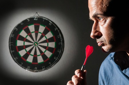 Closeup view of a dart player on a black background concentrating on the dartboard