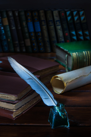 Quill pen and a rolled papyrus sheet on a wooden table with old books Archivio Fotografico