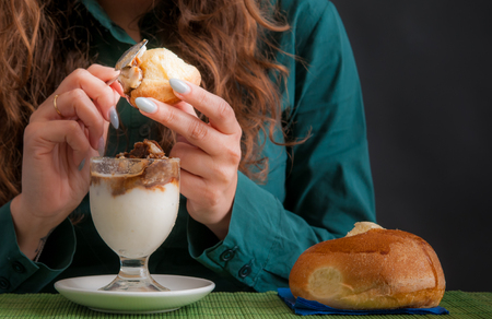 Girl eating a typical sicilian almond and coffee granita with a warm brioche