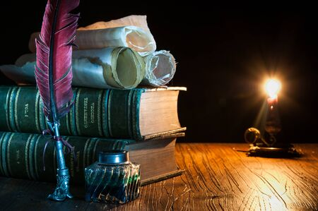 Quill pen and a rolled papyrus sheet on a wooden table with old books at candle light Stock Photo