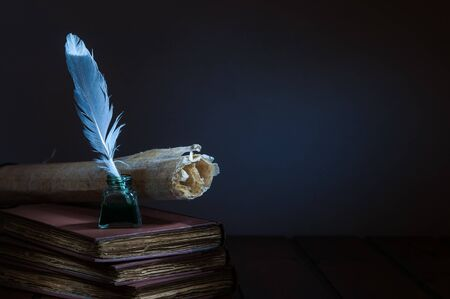 Quill pen and rolled papyrus sheets on a wooden table with old books