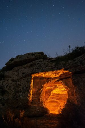 View of a rock-cut tomb by night in the necropolis of Pantalica, Sicily, and starry sky