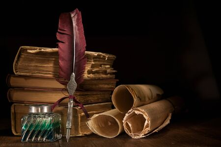 Quill pen and a rolled papyrus sheet on a wooden table with old books, warm effect