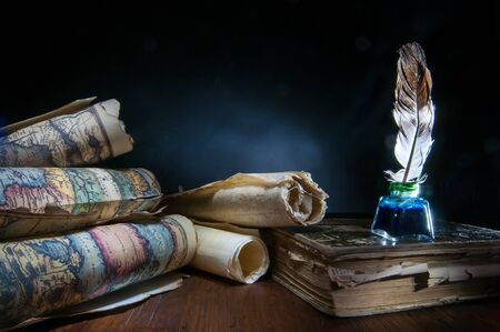 Quill pen, inkwell, old rolled up maps and papers on a dark background