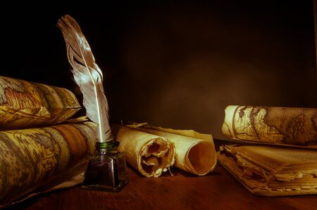 Quill pen, inkwell and old rolled up maps, warm effect Foto de archivo
