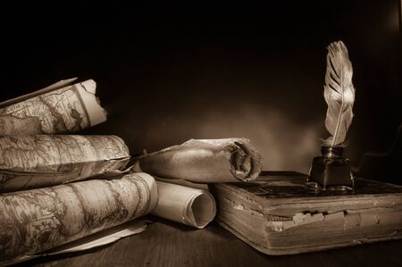 Quill pen, inkwell and old rolled up maps and papers, sepia effect