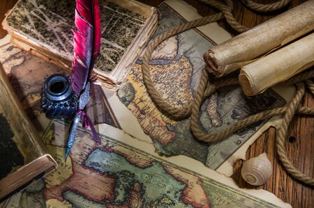 Quill pen, inkwell, old maps and papers on a wooden table