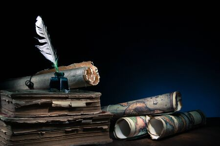 Quill pen, inkwell, old rolled up maps and papers on a dark background Foto de archivo