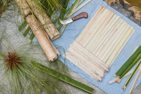 Strips obtained from the stem of papyrus plant with a typical knife and a finished rolled up sheets