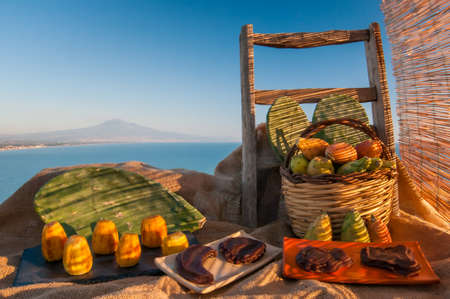 Prickly pears and some mustard shapes on a table with a piece of jute
