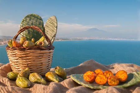 Prickly pears in a wicker basket and some mustard shapes on a table Stock Photo