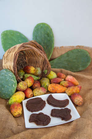 Prickly pears and some mustard shapes on a table on a piece of jute Stock fotó