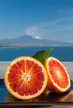 Cut oranges on a wooden table with blue sea and Mount Etna in the background 版權商用圖片