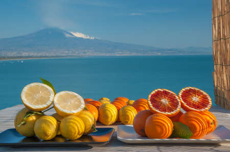 Cut oranges and lemons on a wooden table with blue sea and Mount Etna in the background