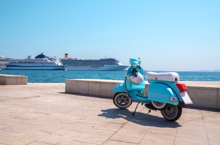 Blue scooter stands on the waterfront on the background of cruise ships in sunny weather 스톡 콘텐츠