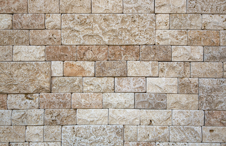 concrete surface finishing: Part of the wall of natural stone beige porous structure. Finishing stone rectangular different shape and size.