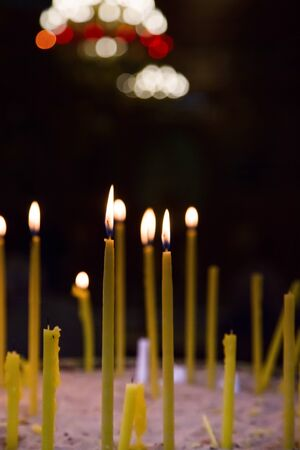 easter candle is burning: Lighted wax candles in a church burning in the twilight Stock Photo