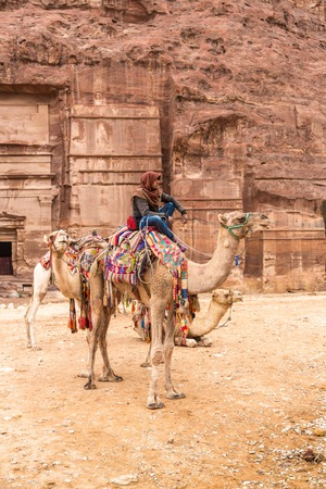 petra  jordan: Petra, Jordan - October 26, 2015: Bedouin on a camel. Tour guide.  A walk on a camel. The service for tourists. The rainy season in Jordan. Petra is one the New Seven Wonders of the World.