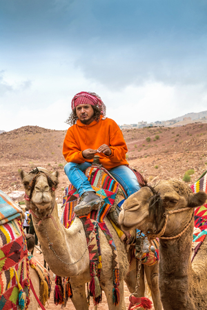 petra  jordan: Petra, Jordan - October 26, 2015: Bedouin on a camel. A walk on a camel. The service for tourists. Tour guide. The rainy season in Jordan. Petra is one the New Seven Wonders of the World. Editorial