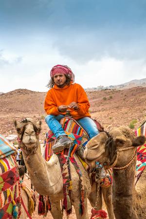 guia turistico: Petra, Jordania - 26 octubre 2015: beduina en un camello. Un paseo en camello. El servicio para los turistas. Guía turístico. La temporada de lluvias en Jordania. Petra es una de las nuevas siete maravillas del mundo. Editorial