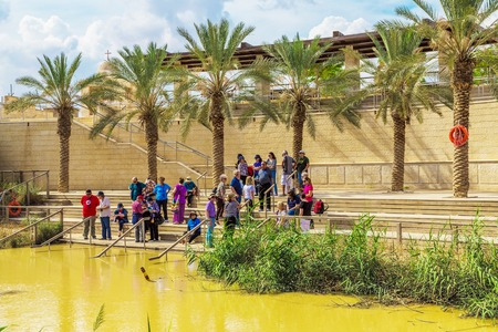 holyland: Jericho, Israel - October 27, 2015: Tourists near the Sacred water of the River Jordan. River where Jesus of Nazareth was baptized by John the Baptist. The border between Jordan and Israel
