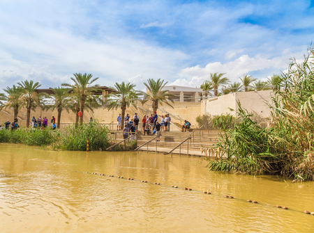 baptized: Jericho, Israel - October 27, 2015: Tourists near the Sacred water of the River Jordan. River where Jesus of Nazareth was baptized by John the Baptist. The border between Jordan and Israel