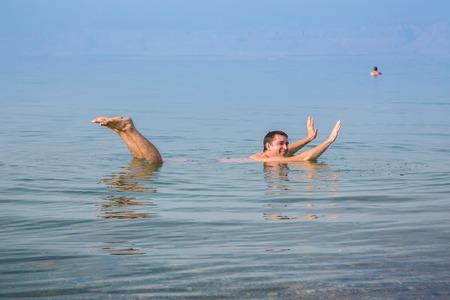 Man Toben im Toten Meer in Jordanien. Dichtes salzigem Wasser schiebt den Mann aus. Lächelnder Mann schwimmt im Meer.