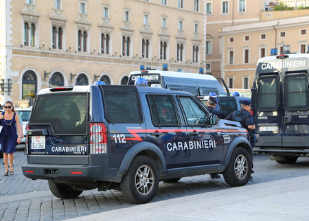 carabineer: Rome, Italy - June 25, 2014: Police stand near a police car on one of the main streets of Rome during a public event.