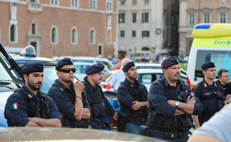 carabineer: Rome, Italy - June 25, 2014: A group of armed police officers standing near the police car on one of the main streets of Rome during a public event. Police are closely monitoring what is happening around.