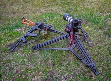 barrel bomb: Odessa, Ukraine - December 02, 2015: The camera Canon and two machine guns lying on the grass. War correspondent concept.