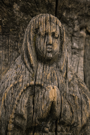 antiques: Virgin Mary carved on ancient wooden icon. The wooden figure of the Virgin Mary. Old wooden icon of the Virgin Mary with a close-up. Portrait of the Virgin Mary carved from wood. Cracked figurine. Stock Photo