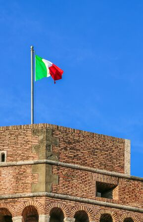 Vatican, Italy - June 26, 2014: Italy flag on an old fortress fluttering in the wind in the rays of the setting sun