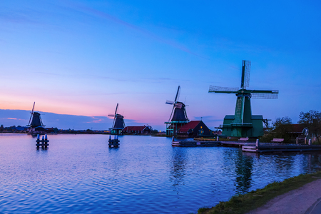zaan: Dutch mill by evening. Sunset in landscape with mill the Netherlands. Dutch windmill at sunset at a lake. River Zaan with four windmills lined up at De Zaanse Schans in Zaandam, Netherlands Stock Photo