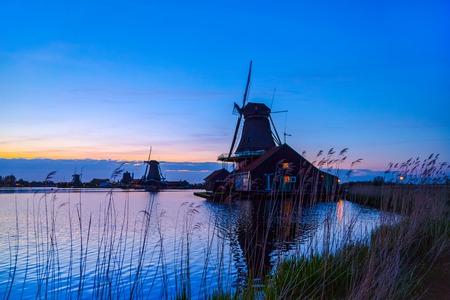 zaan: Evening River Zaan with Dutch windmills in Zaandam, Netherlands. Sunset landscape with windmills and field wild herbs and flowers. Sunset landscape with windmills and field wild herbs and flowers. Stock Photo
